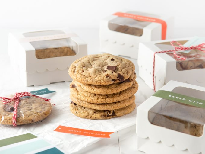 Stack of Copycat Panera Chocolate Chip Cookies with Gift Boxes and Tags