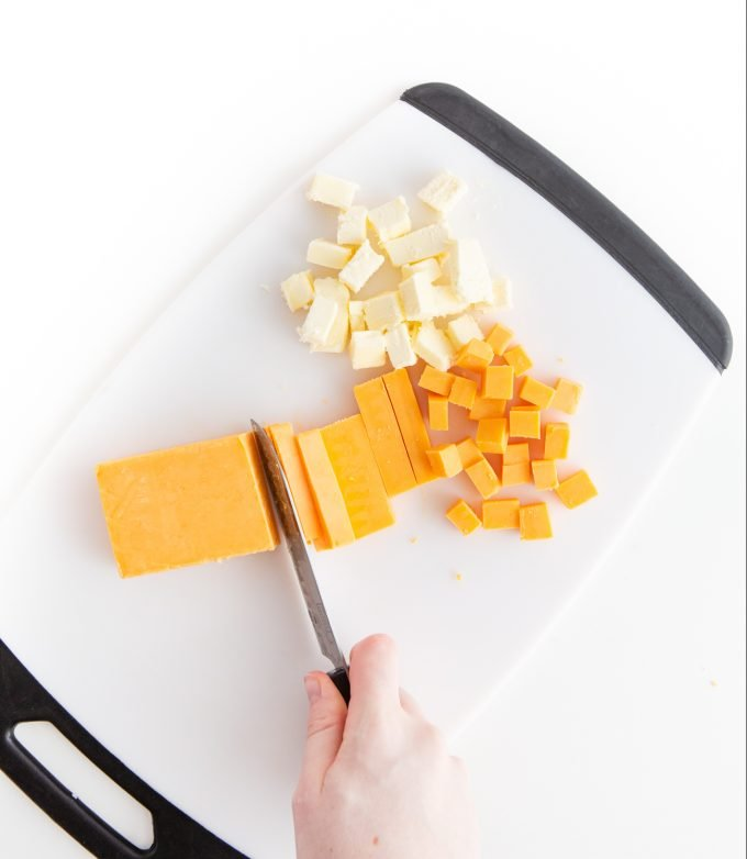 Cutting cheese and butter in small cubes with knife on cutting board to make homemade cheese crackers
