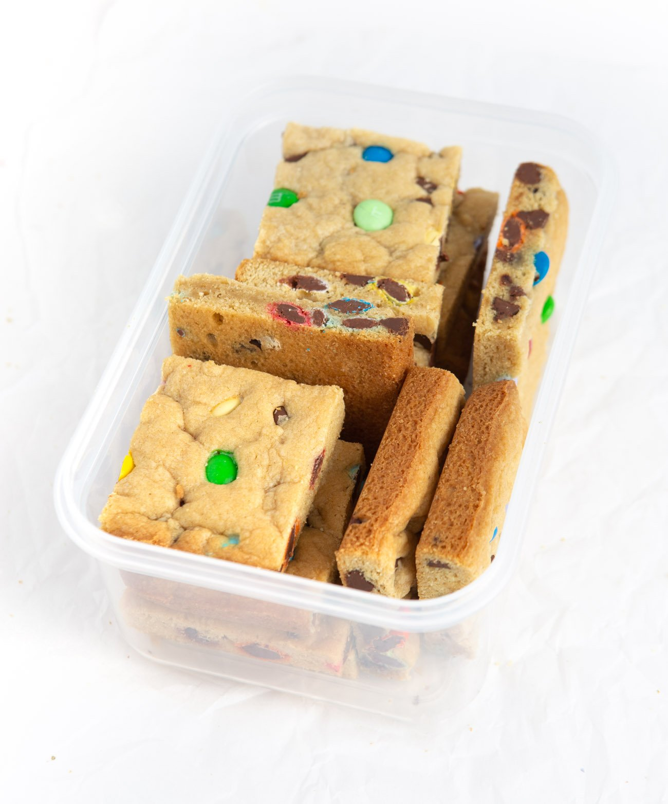 Chewy M&M Cookie bars cut into squares in plastic container for freezing