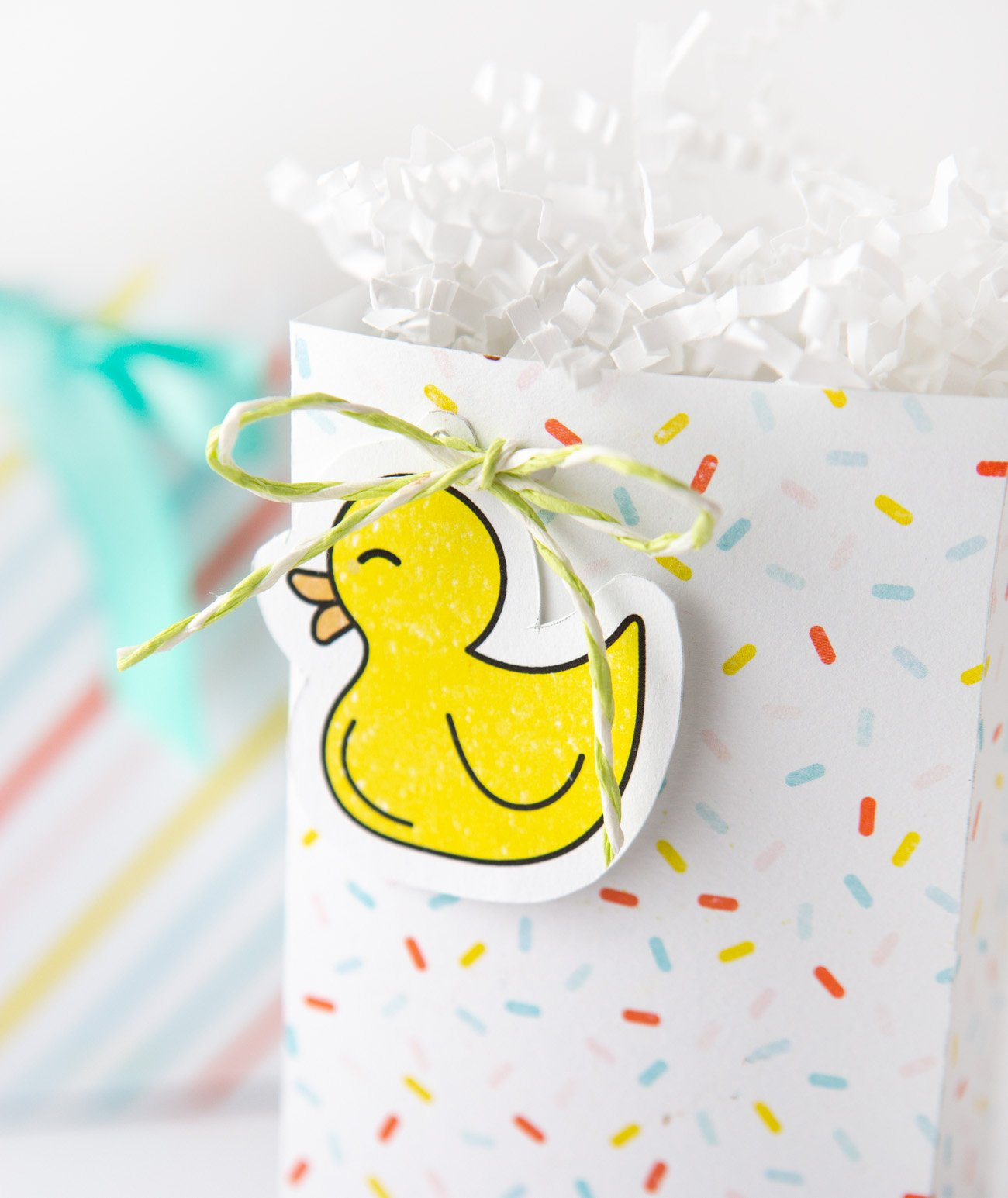 Rubber duck gift tag attached to sprinkle baby shower favor bag