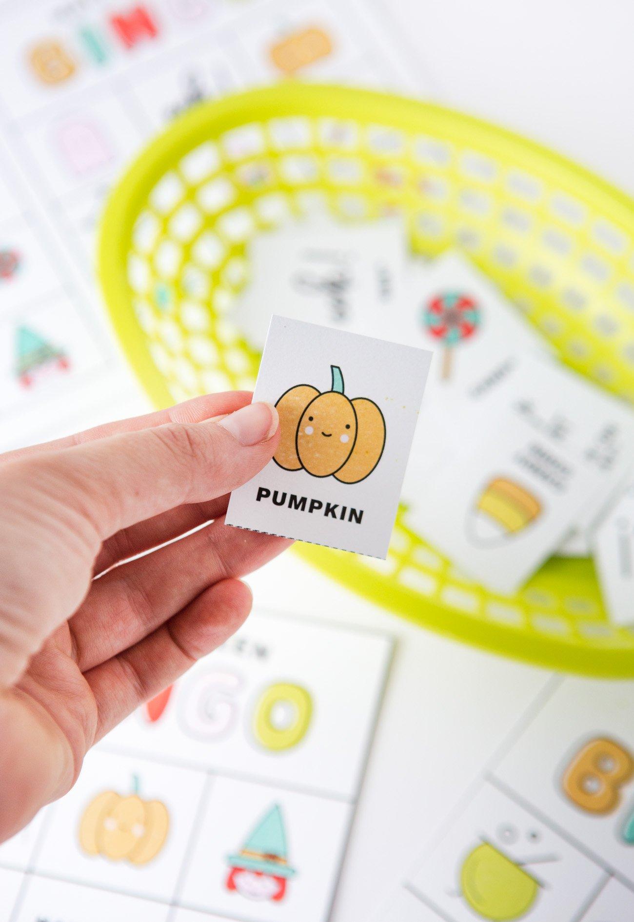 Hand holding pumpkin bingo card for Halloween bingo