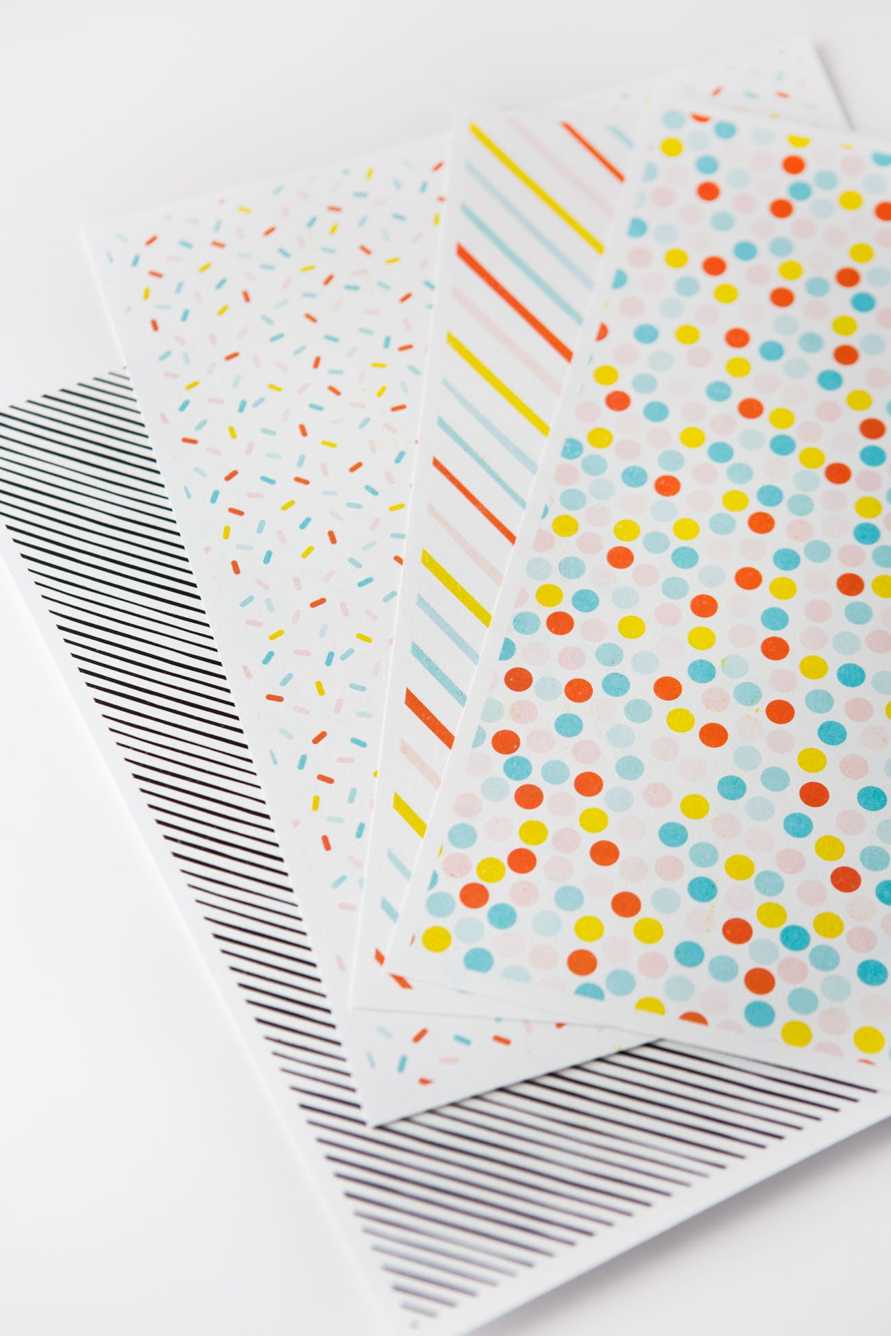 Rainbow printable scrapbook paper in sprinkle pattern, stripe, polka dot, and black and white stripe