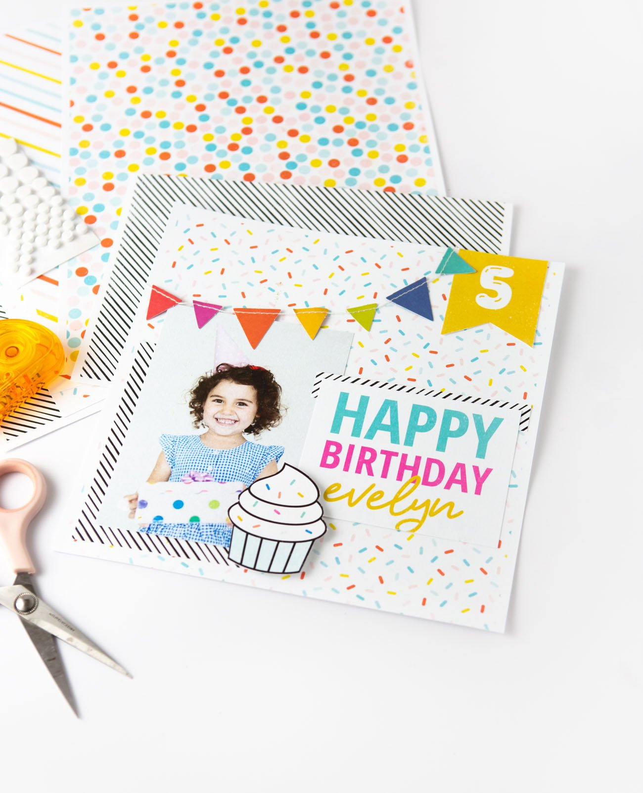 Colorful rainbow scrapbook page design with Happy Birthday text, cupcake, and banner