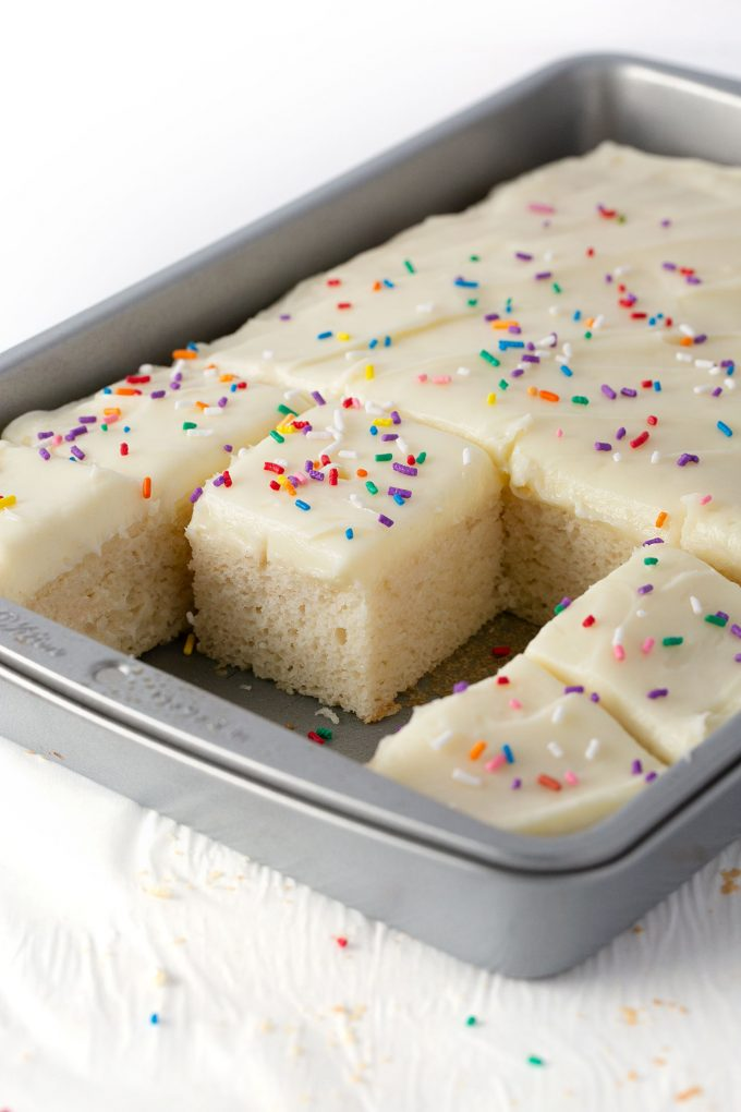 white sheet cake in metal 9x13 pan with white frosting and sprinkles