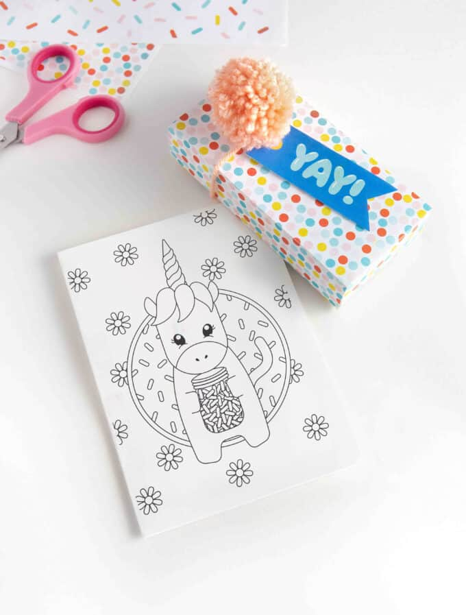 "Printed 5x7 unicorn birthday card with colorful gift box with blue ""YAY"" gift tag and pink pom pom."