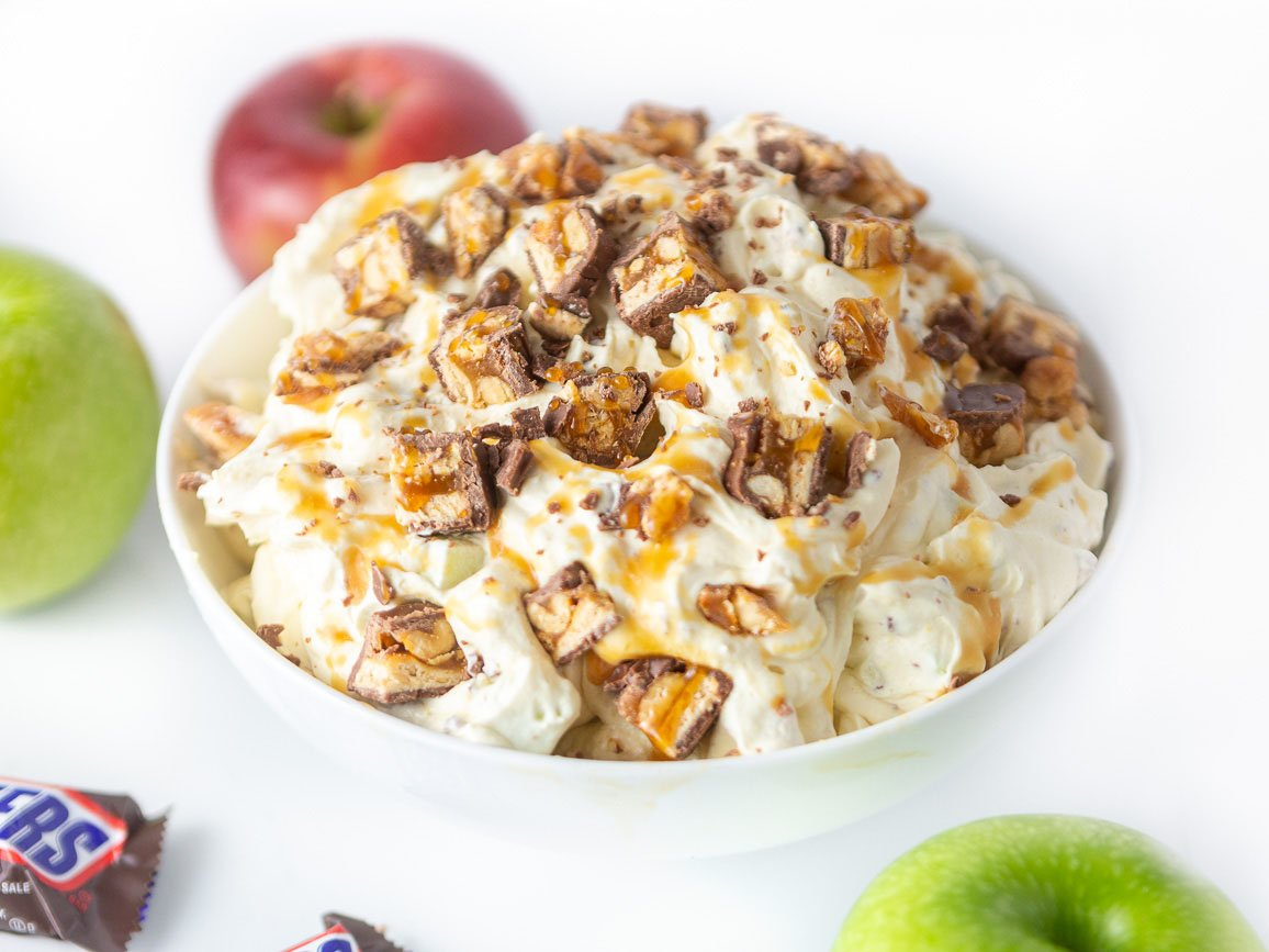 Bowl of creamy apple snickers salad dessert, topped with chopped snickers candy bars, apples, and caramel sauce