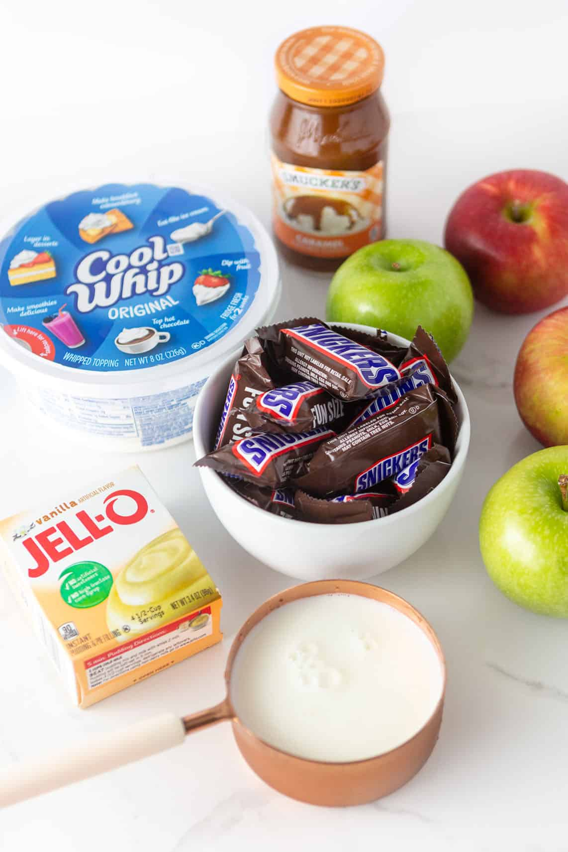 Ingredients for apple snickers salad; includes bowl of snickers, cool whip, a box of instant vanilla pudding mix, milk, apples, and a jar of Smuckers caramel sauce