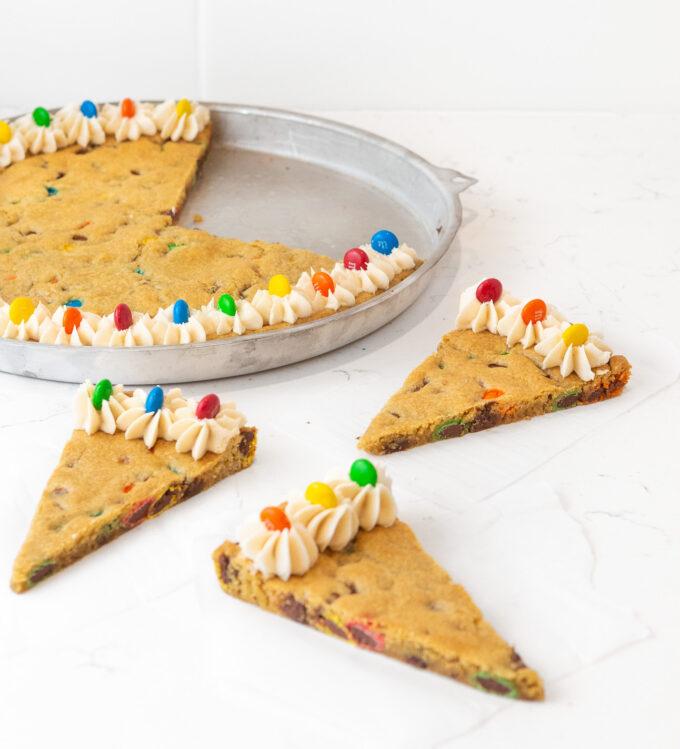 Sliced M&M cookie cake in pan