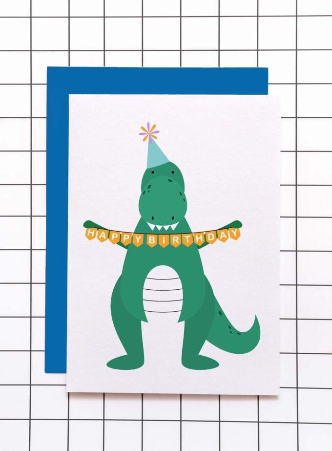 Greeting card of green dinosaur holding happy birthday banner