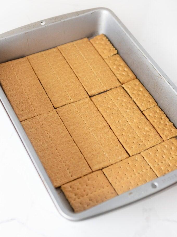 graham crackers lining bottom of 9x13 pan