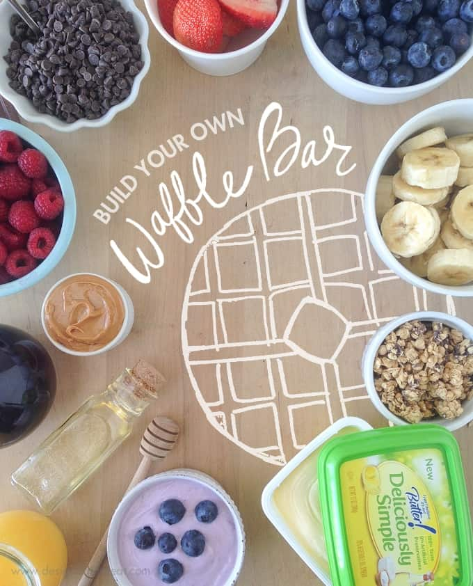 Ingredients and waffle toppings to create DIY Waffle Bar. Includes bowls of fruit, granola, yogurt, and chocolate chips.