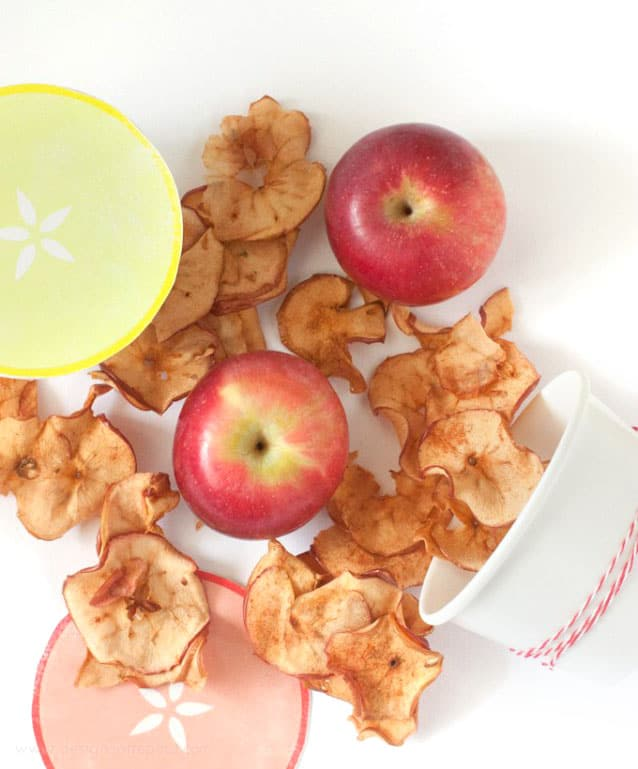 Baked apple chips on table coming out of paper cup for cute packaging idea.