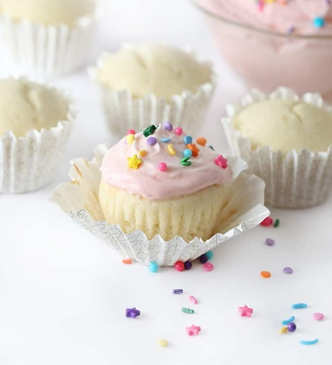 white cupcake with pink frosting and sprinkles in cupcake liner