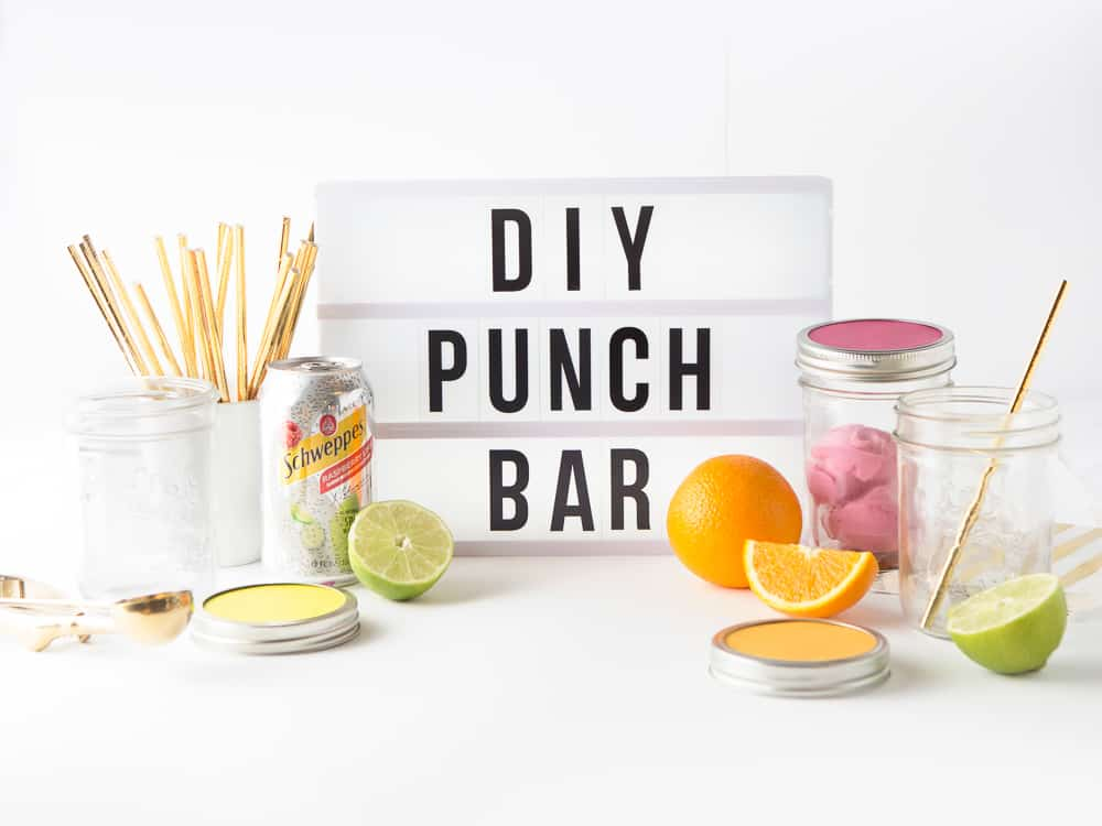 "A white lightbox sign with words, ""DIY Punch"" Bar surrounded by cans of Schweppes sparkling water, mason jars, gold straws, and slices of fruit."