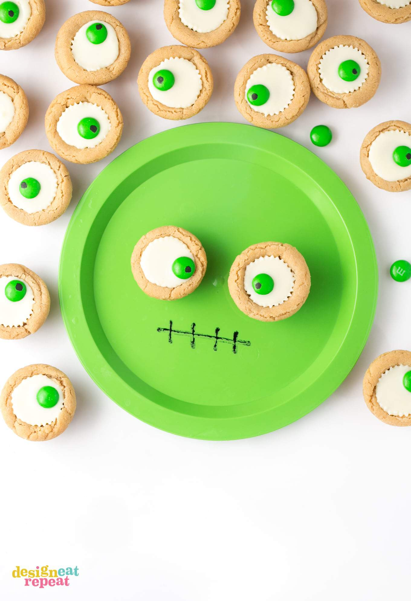Mini white peanut butter cup cookies on green monster face plate.