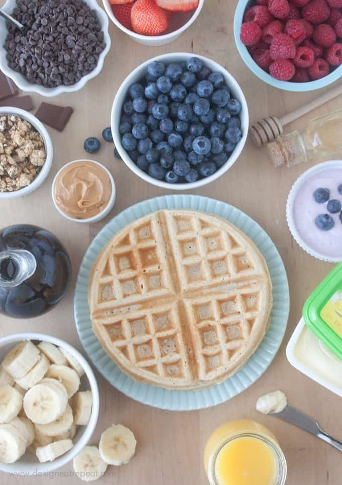 Overhead picture of waffle bar with waffle toppings. Blueberries, raspberries, peanut butter, bananas, and more.