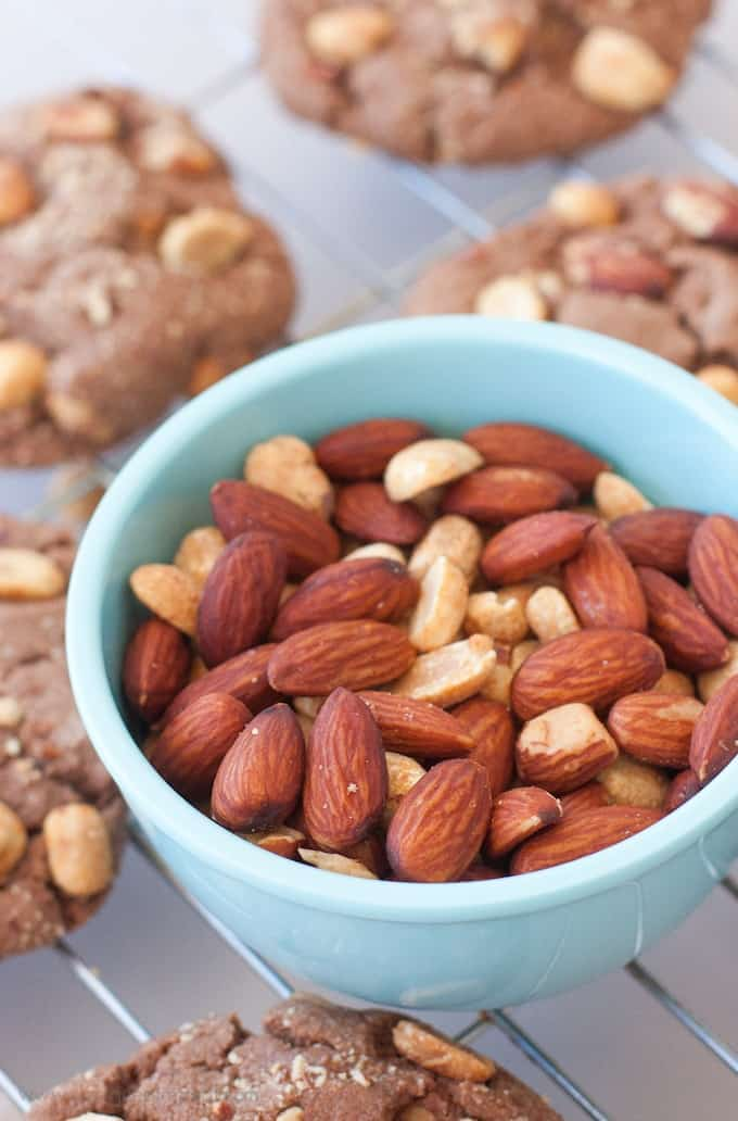 Blue bowl of almonds sitting on top of wire cooling rack.