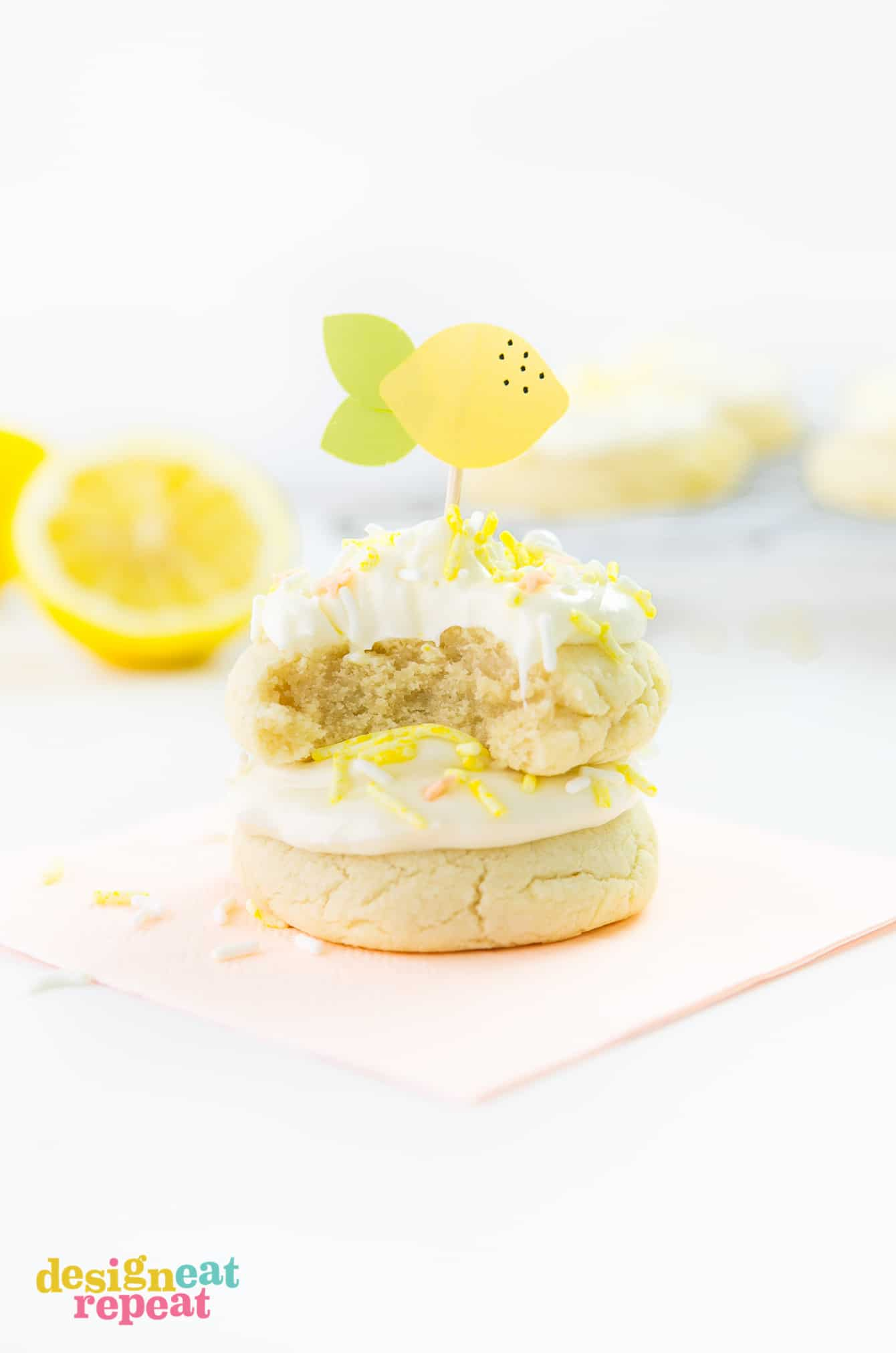 Stack of thick lemon sugar cookies with frosting, yellow sprinkles, and paper lemon toothpick topper on top.