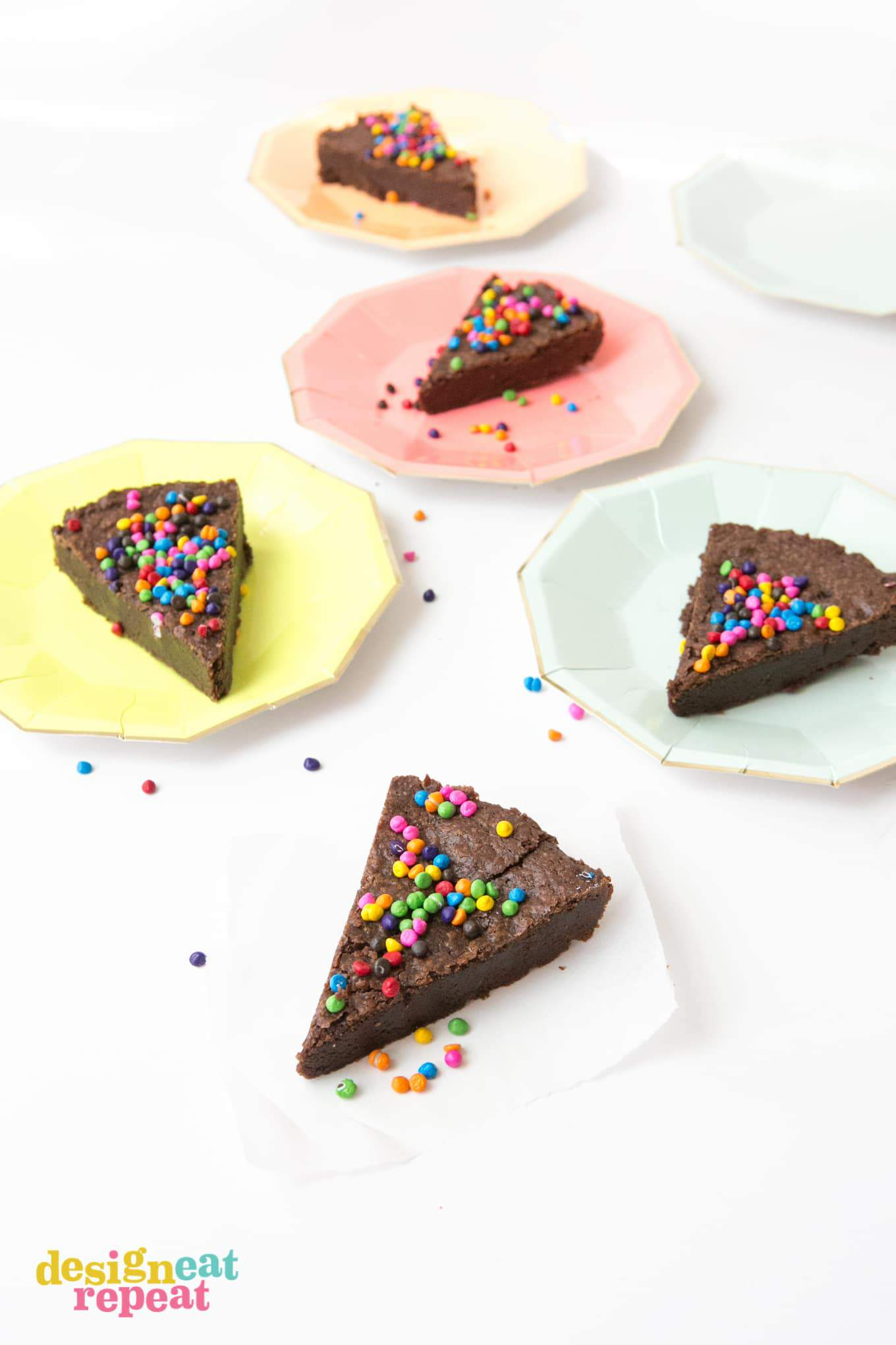 Triangle slices of brownie pie with rainbow chocolate chip sprinkles on top.