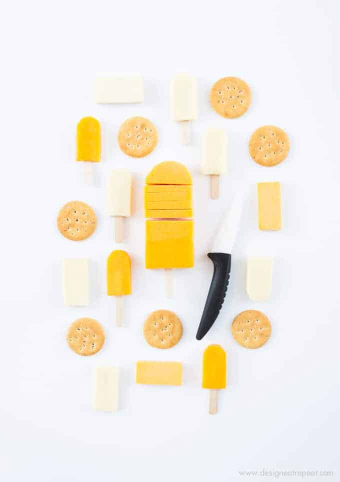 Turn cheese slices into mini popsicles with this fun cheese board idea! Fun way to mix up the Superbowl or holiday cheese tray!