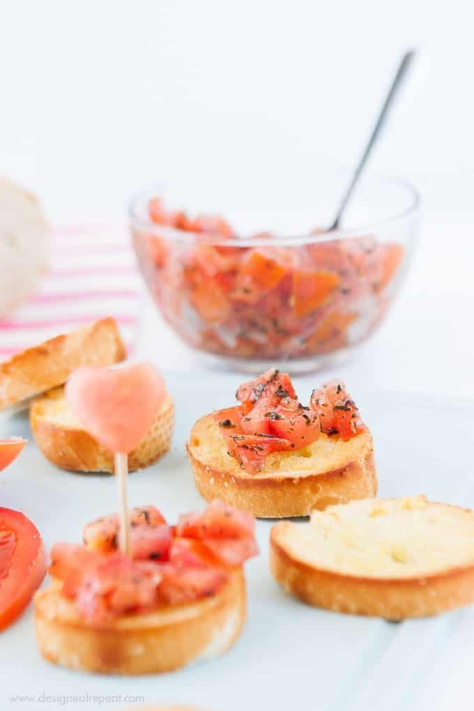 Use a mini heart cookie cutter to turn ordinary bruschetta into a festive Valentine's appetizer! Check out the recipe on Design Eat Repeat blog!