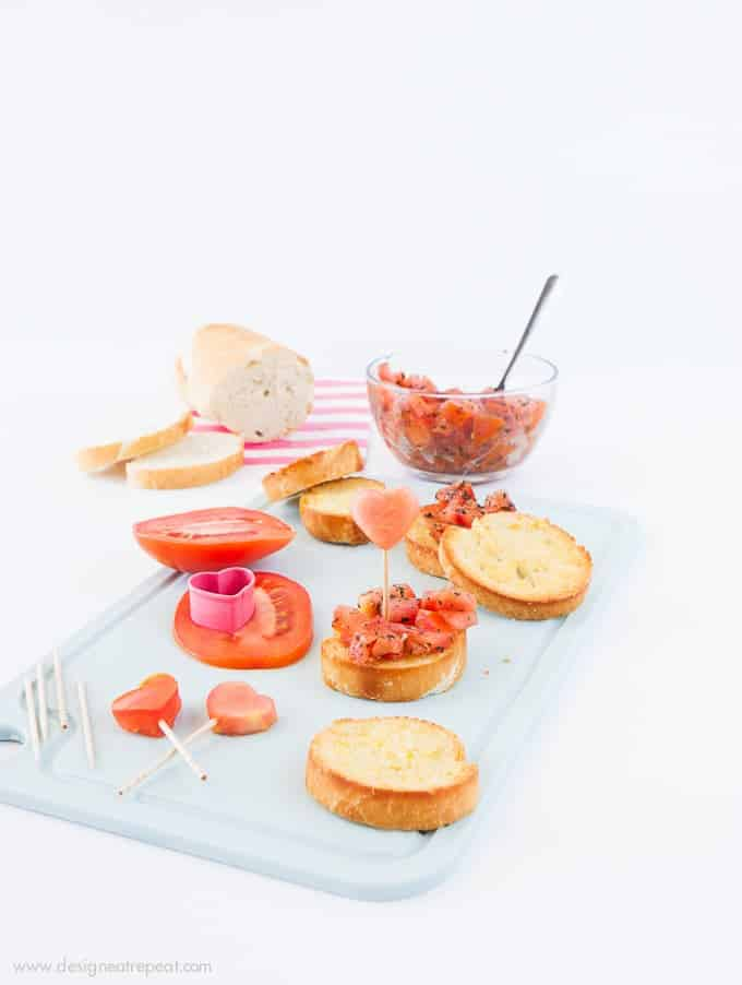 Use a mini heart cookie cutter to turn ordinary bruschetta into a festive Valentine's appetizer! Check out the recipe on Design Eat Repeat!
