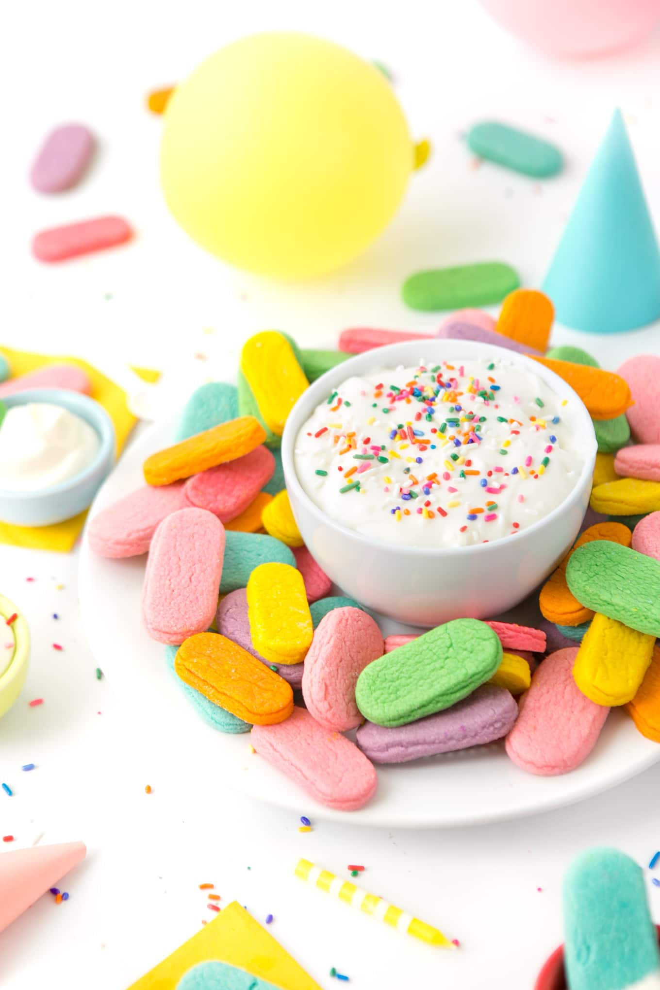 Plate of rainbow sprinkle sugar cookies with a bowl of cream cheese frosting in a party scene.