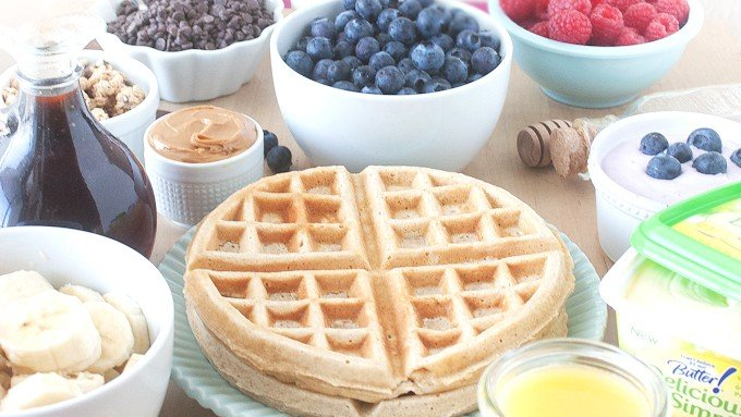 Plate of whole wheat waffles, bowl of blueberries, raspberries, bananas, peanut butter, and chocolate chips.