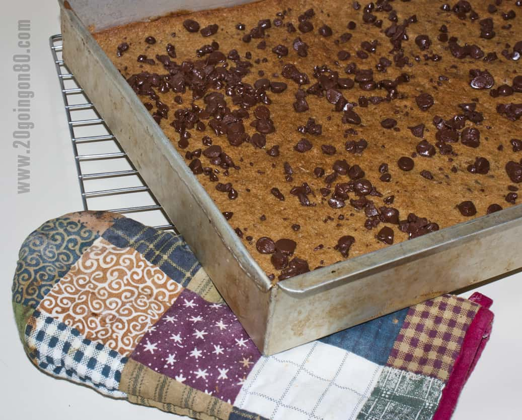 Large rectangle pan of cookie cake on wire rack with oven mitt.