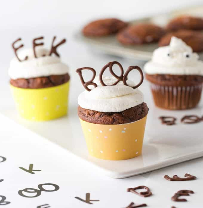 Cupcake topper made with chocolate that spells BOO with orange cupcake wrapper