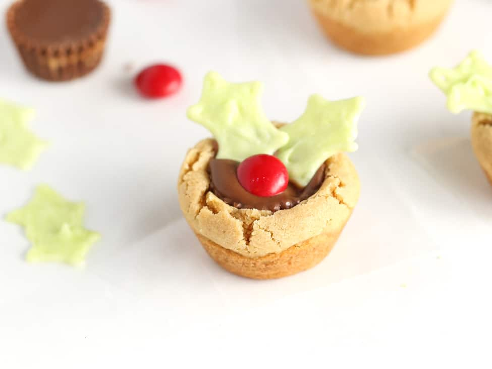 Reeses peanut butter cup cookie decorated like holly leaf to make easy Christmas holly cookie cups.