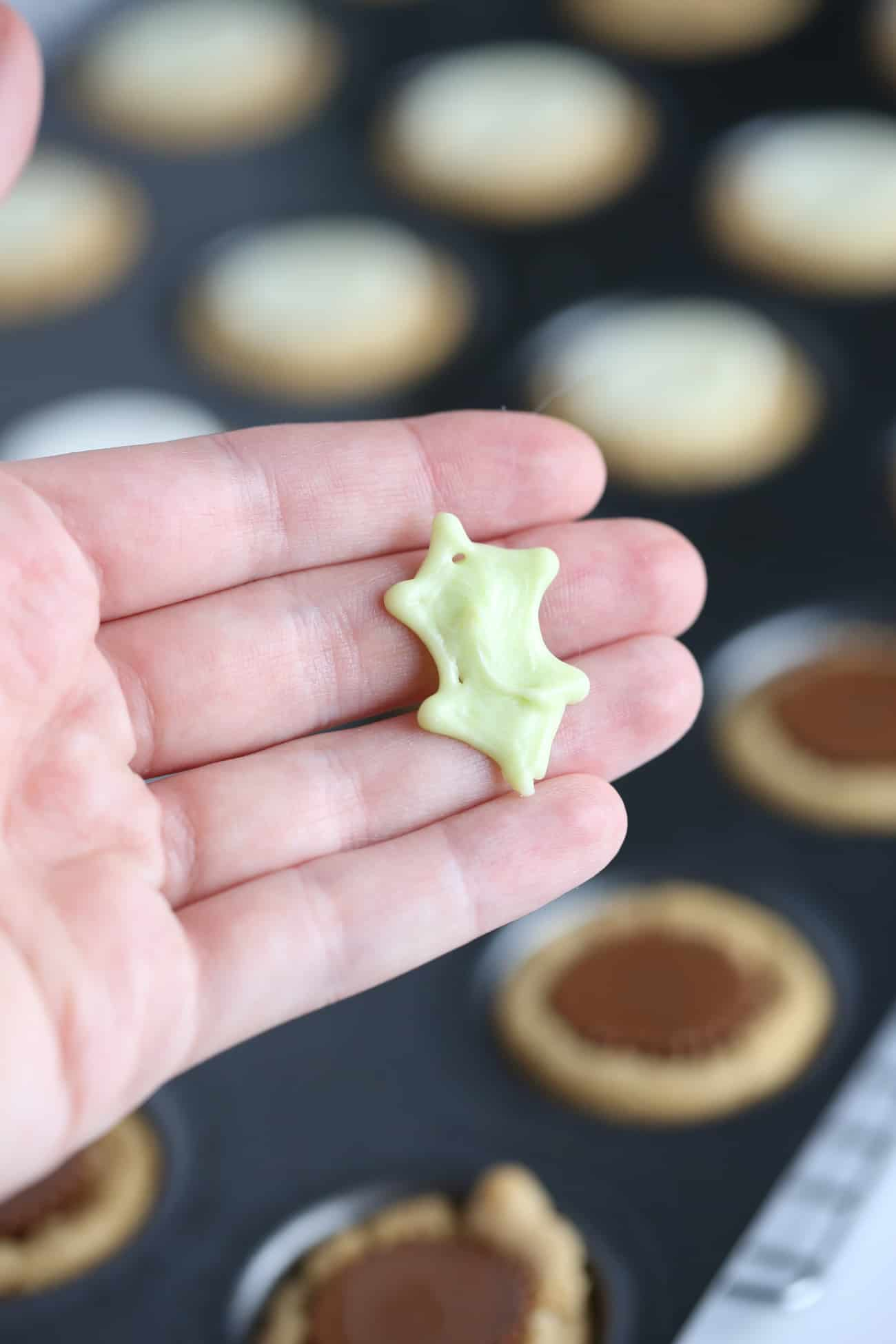 Hand holding white chocolate green holly leaf to make Holly leaf printable template to make easy Christmas holly cookie cups!
