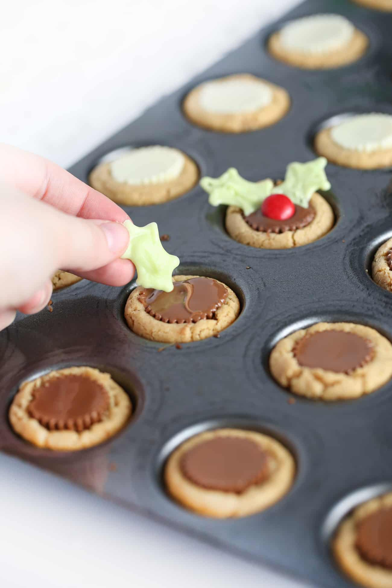 Hand placing white chocolate holly leaf into Reeses peanut butter cup cookie to make easy Christmas holly cookie cups.