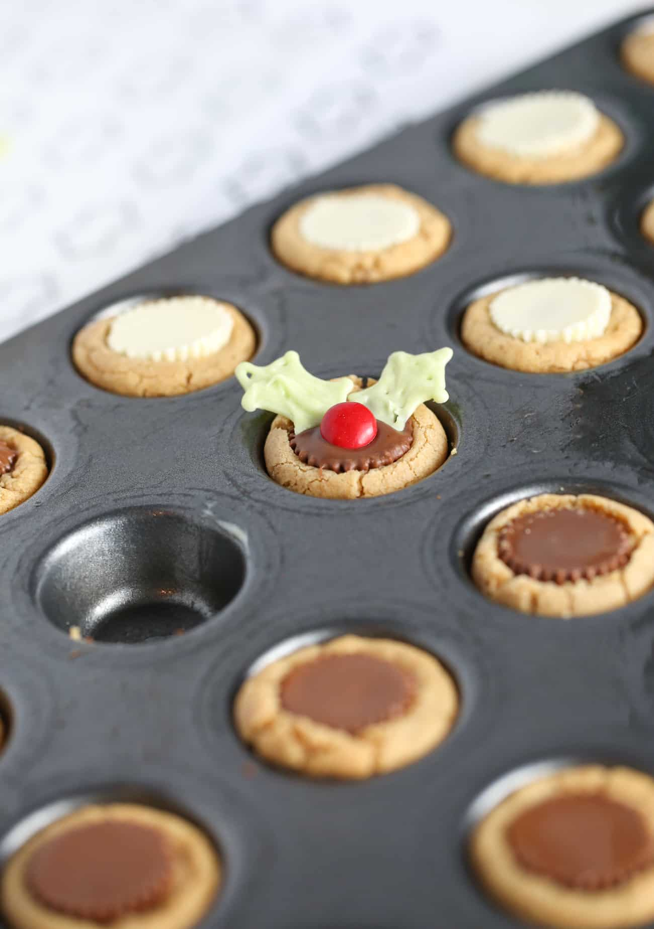 Mini muffin tin with peanut butter cookie cups to make easy Christmas holly cookie cups.