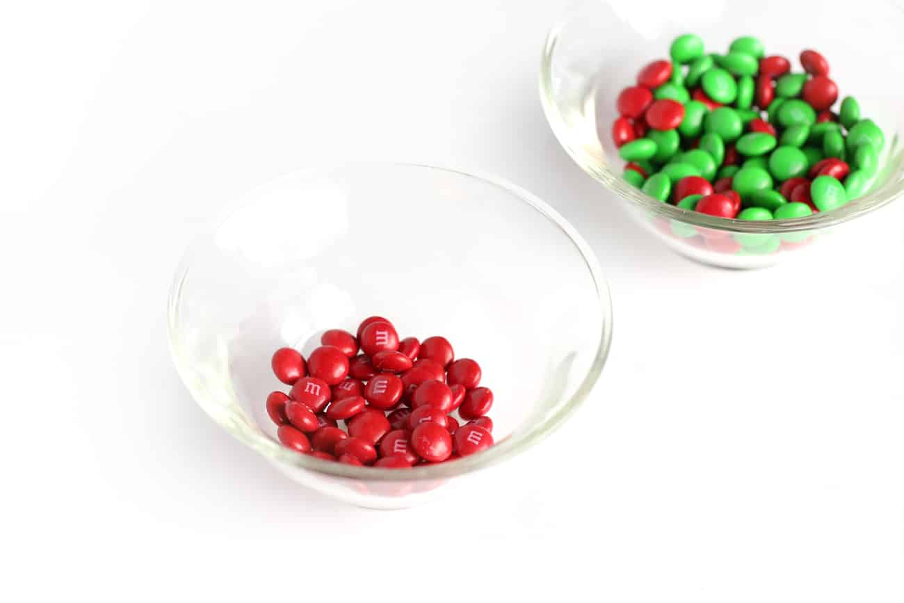 Small glass bowl of red M&M's to make easy Christmas holly cookie cups!