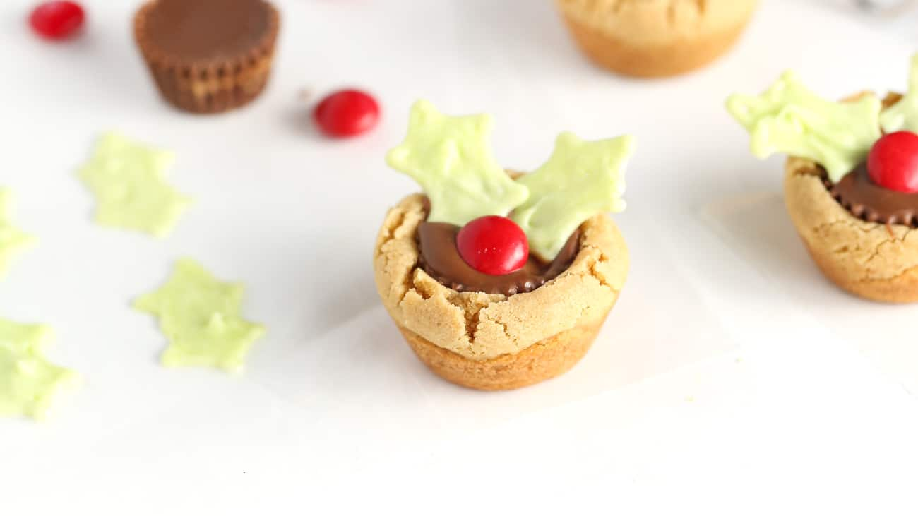 reeses peanut butter cup cookie decorated like holly leaf to make easy christmas holly cookie cups