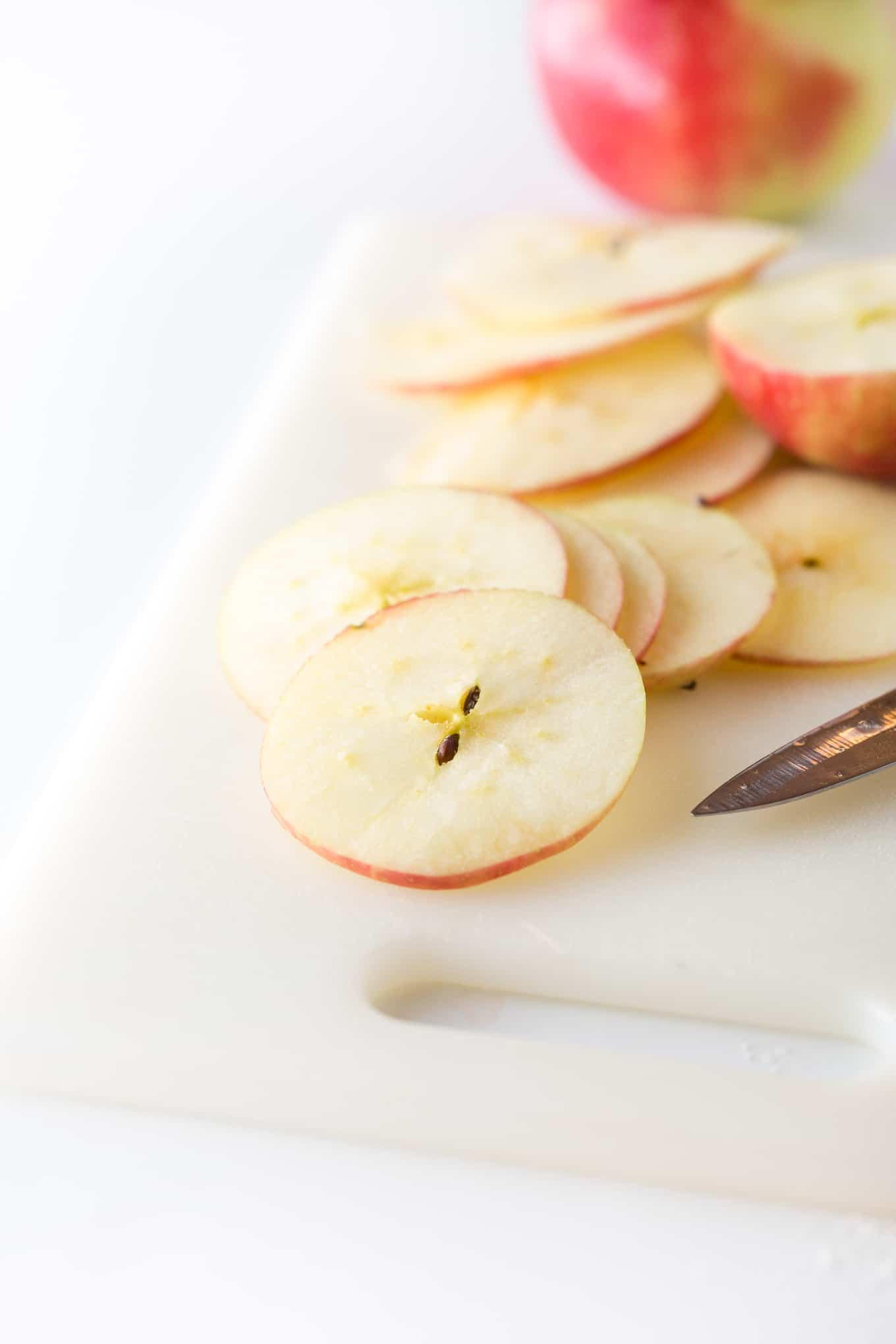Cutting slices of honeycrisp apples with knife for apple chips.