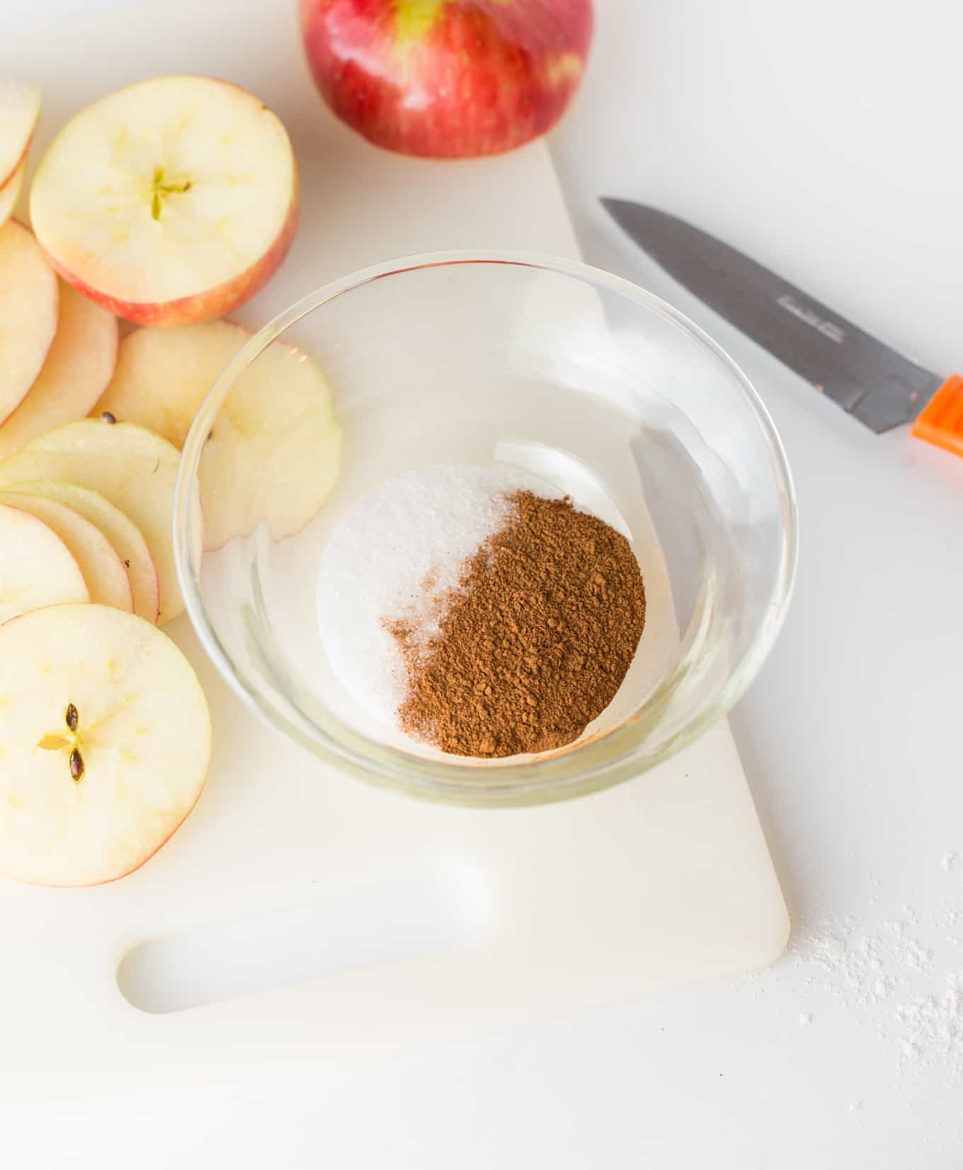 Glass bowl of cinnamon and sugar for apple chips with knife and apple slices.
