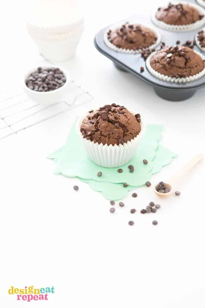 Jumbo Double Chocolate Zucchini Muffin on mint scalloped napkin, with more muffins in cupcake tin in the background.