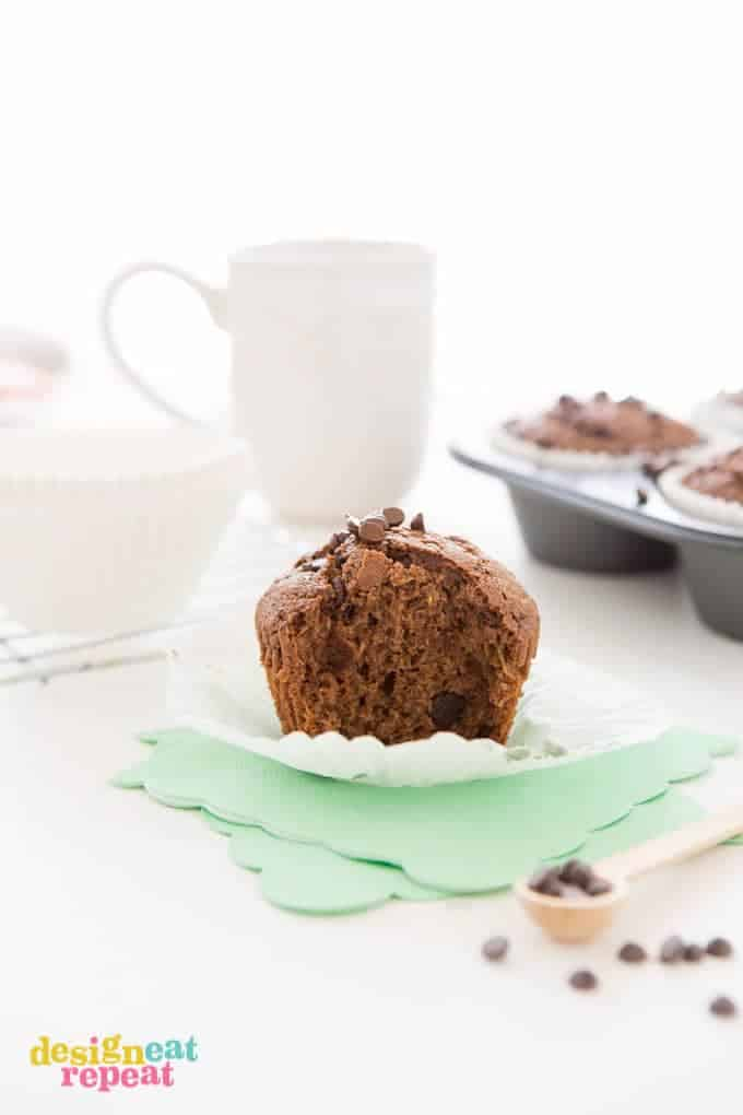 Chocolate Zucchini Muffin with bit taken out, placed on top of mint colored napkin.