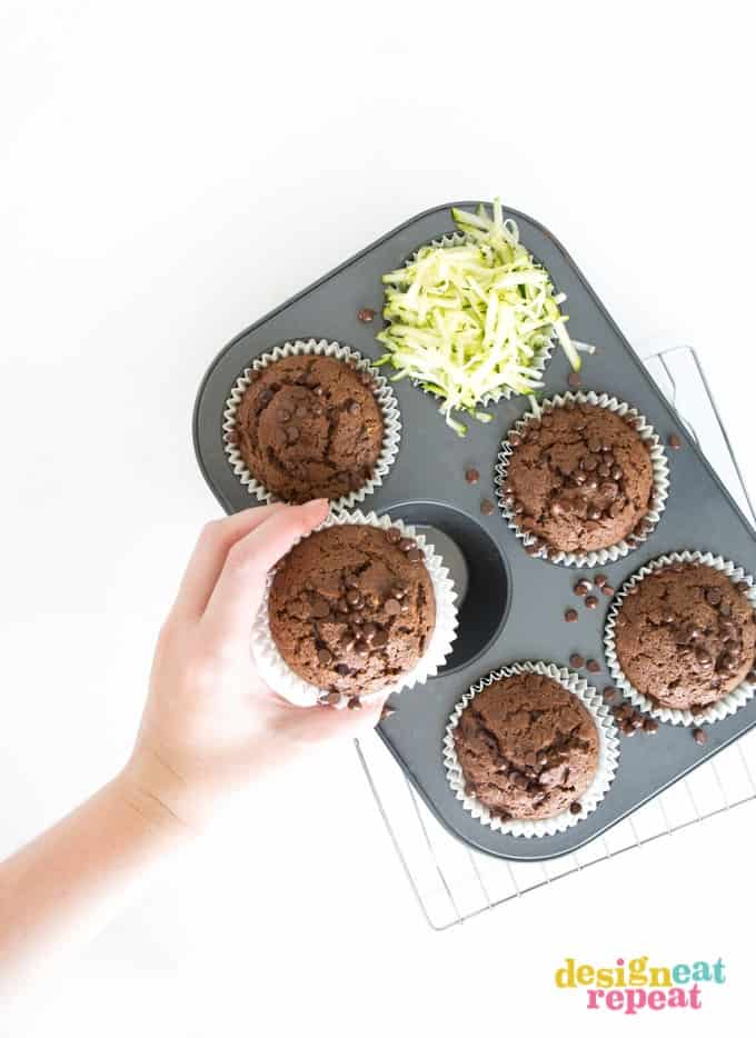 Hand reaching out and picking up chocolate muffin from cupcake pan.