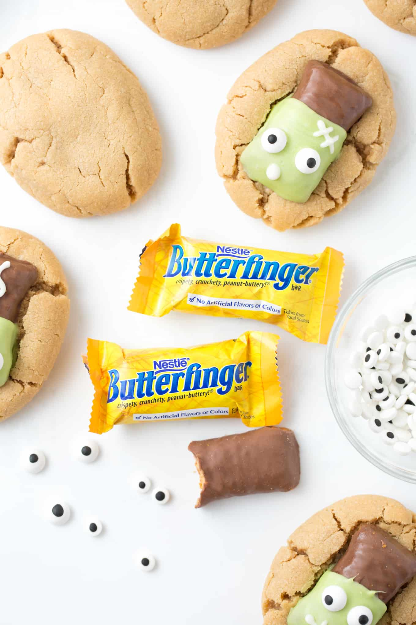 Peanut butter cookies topped with Butterfinger fun size candy bars that have been decorated to look like Frankenstein.