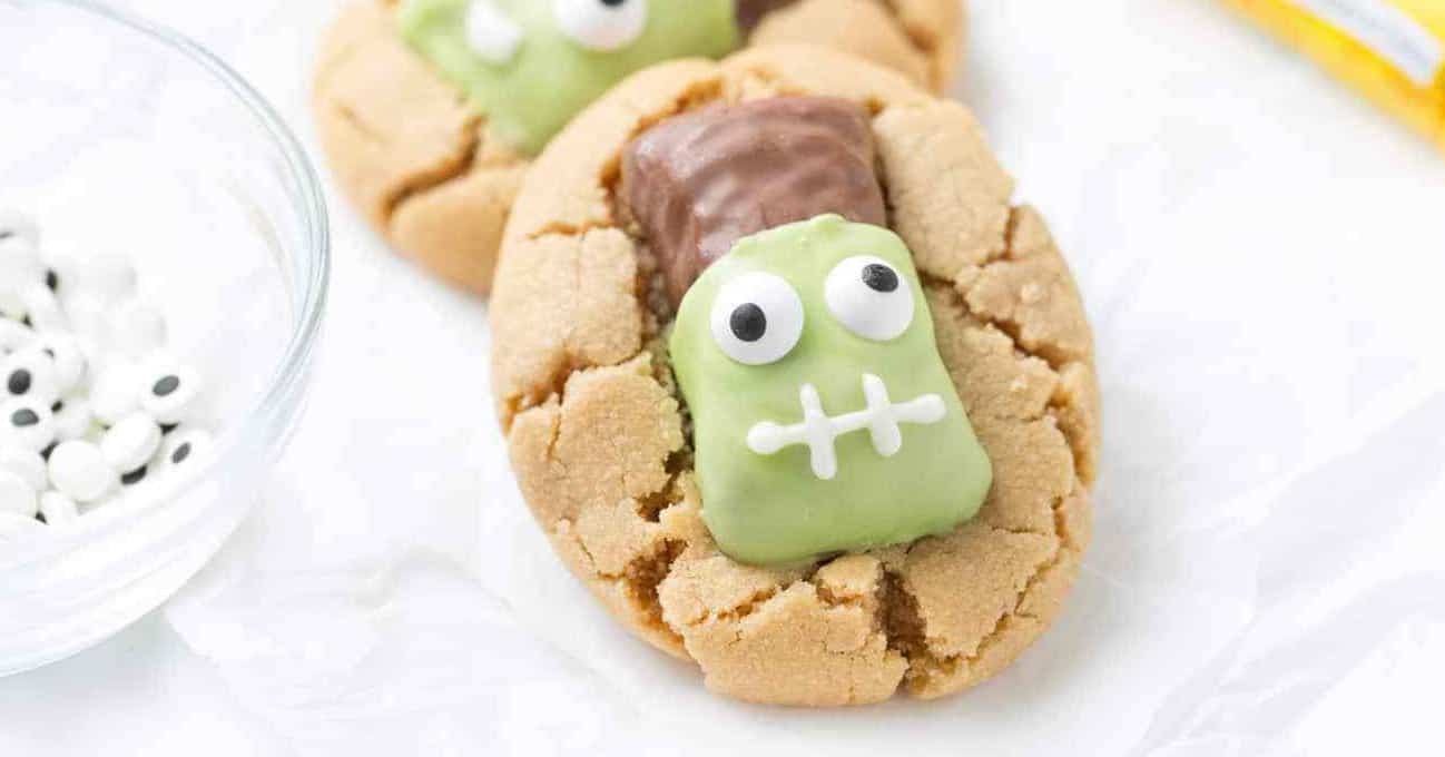 Close up shot of peanut butter cookies topped with Butterfinger fun size candy bars that have been decorated to look like Frankenstein.
