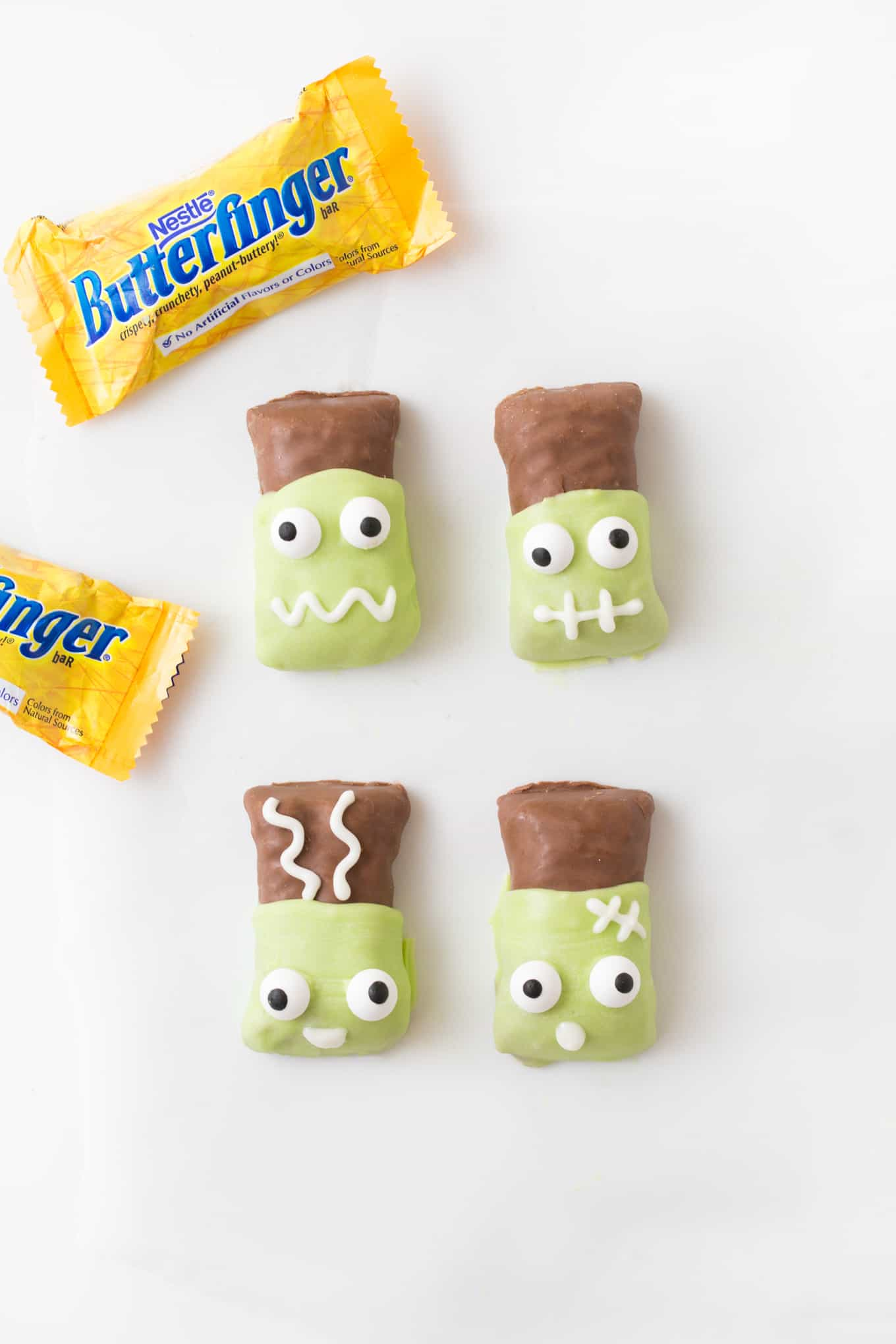 Butterfinger candy bars that have been dipped in melted green almond bark then decorated with candy eyeballs to look like Frankenstein and Frankenstein's bride.