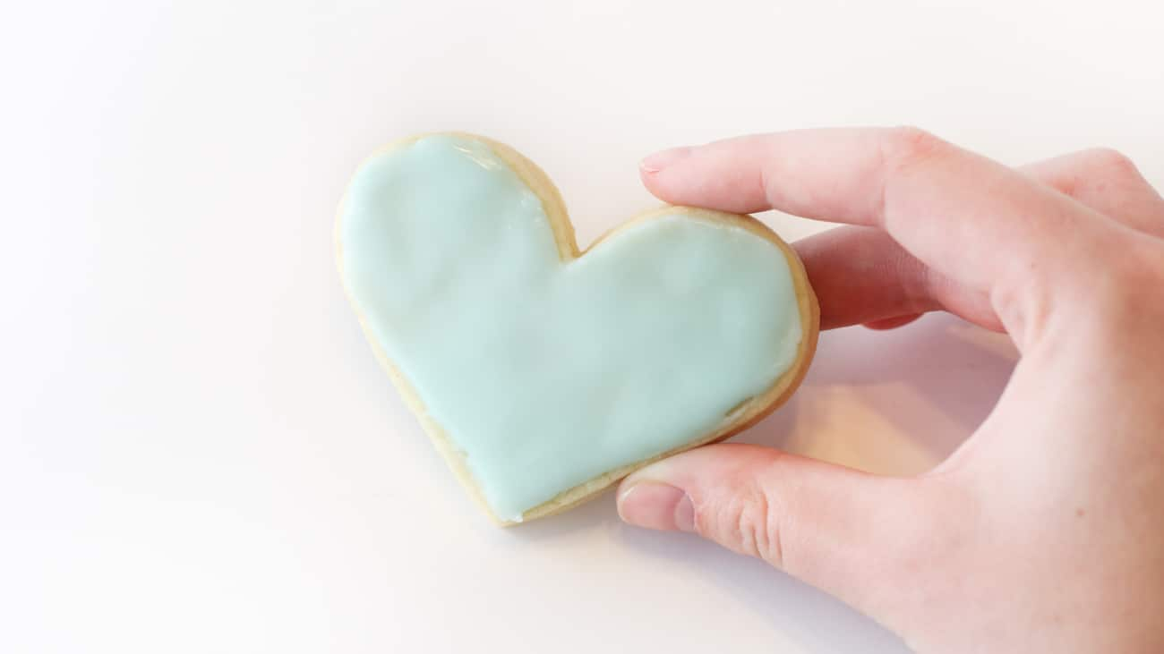 Hand holding blue heart sugar cookie.
