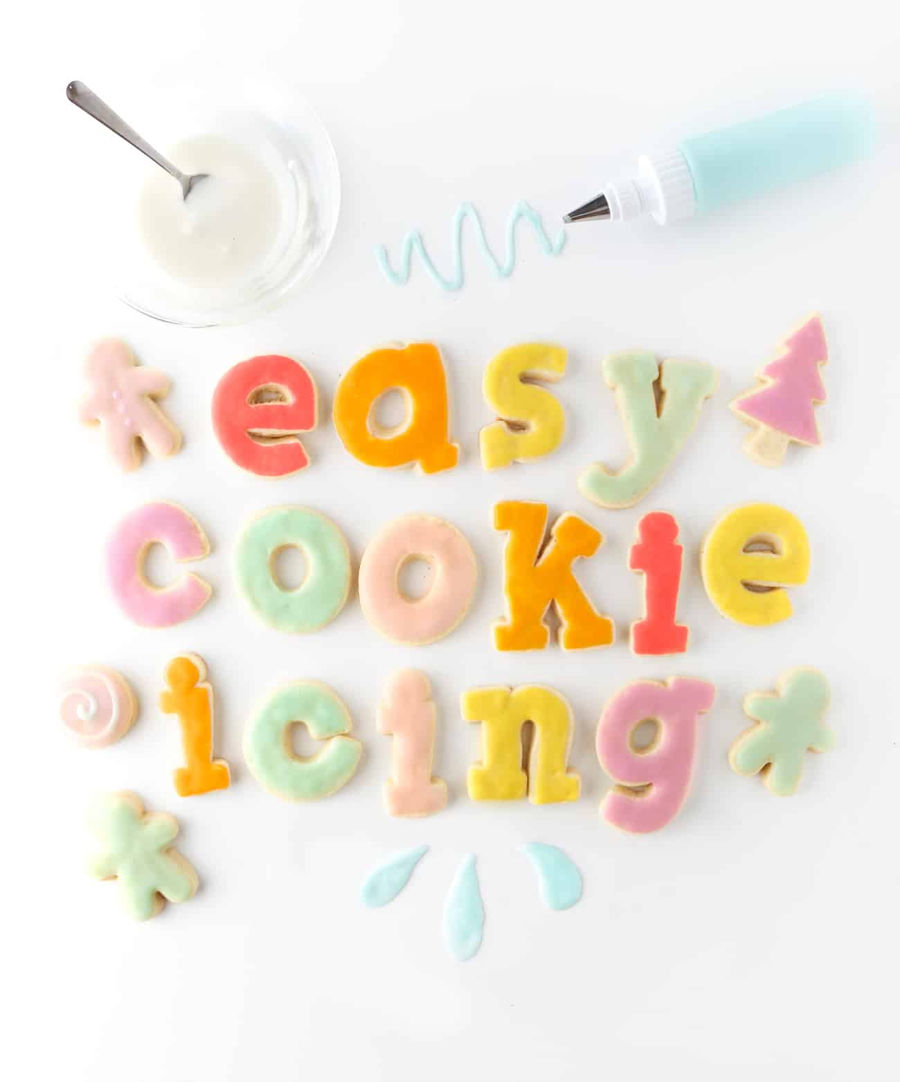 Rainbow sugar cookies spelling out the words Easy Sugar Cookie Icing. White bowl of icing with bottle of blue icing.