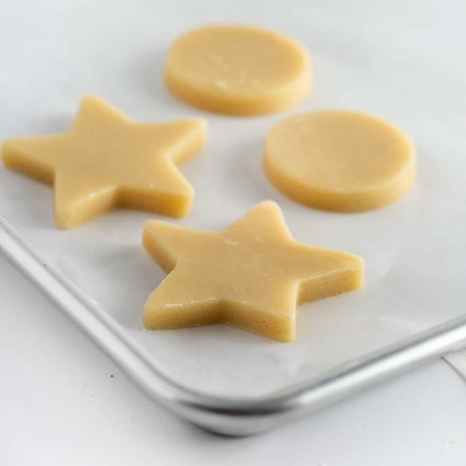Star and circle shaped sugar cookie dough on baking tray