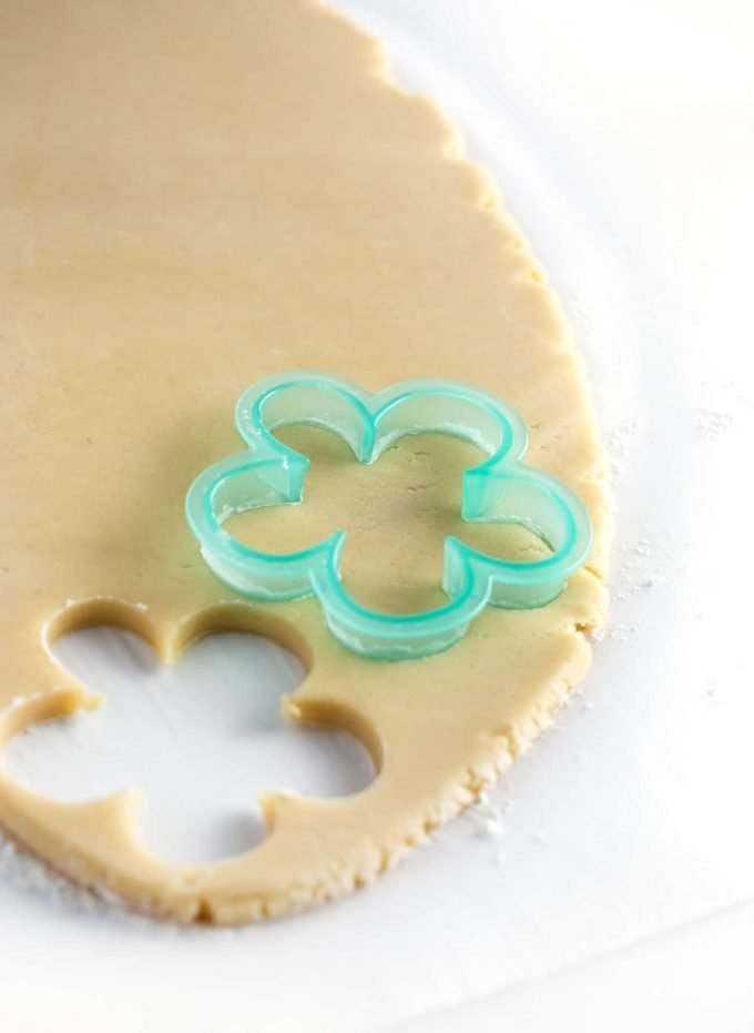 Blue flower cookie cutter cutting out sugar cookie dough
