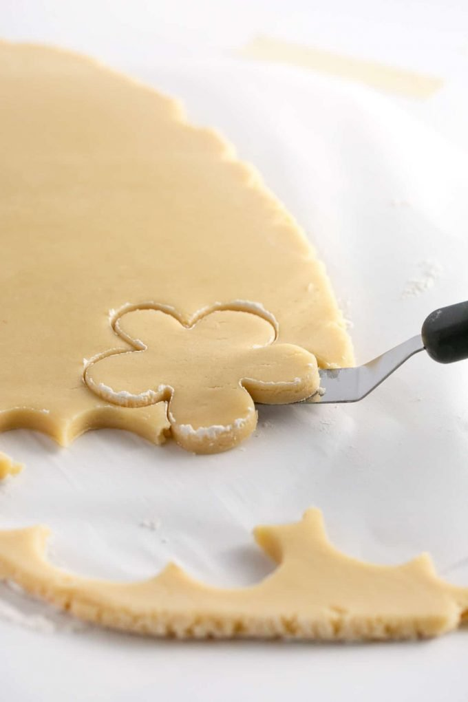 Lifting cut flower sugar cookie dough off of parchment paper with offset spatula
