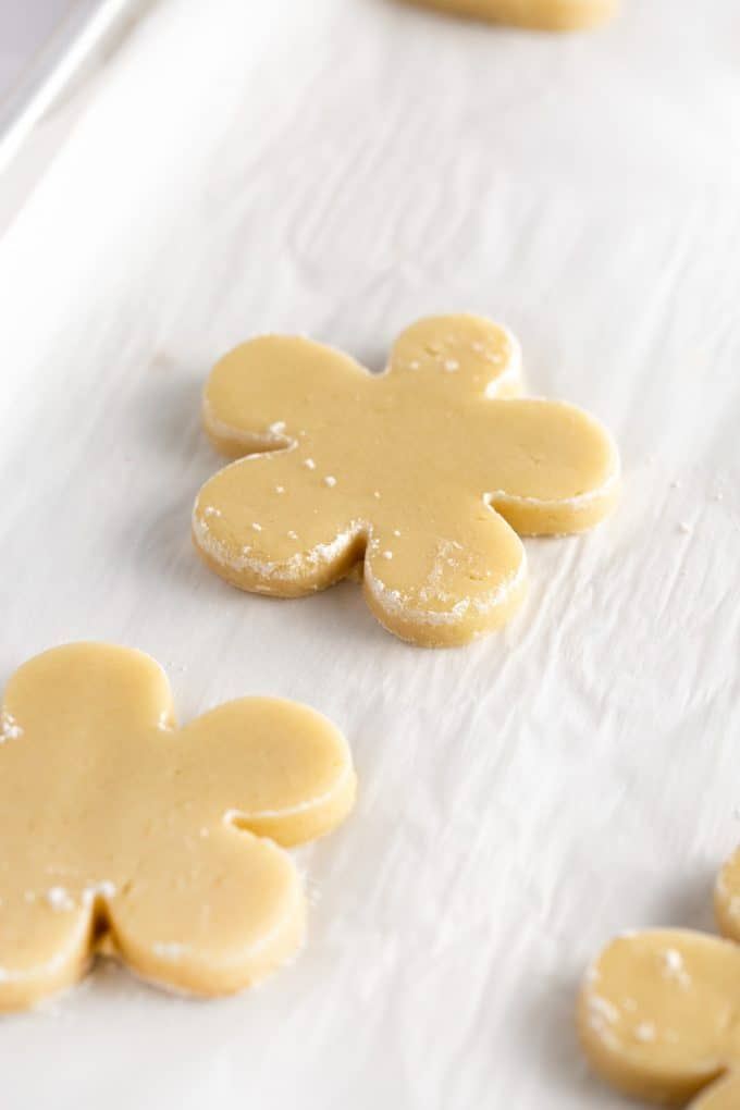 Flower shaped sugar cookie dough on baking tray